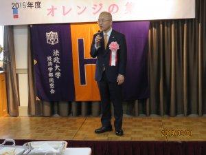 パーティーで挨拶する佐々木郁夫校友会会長
